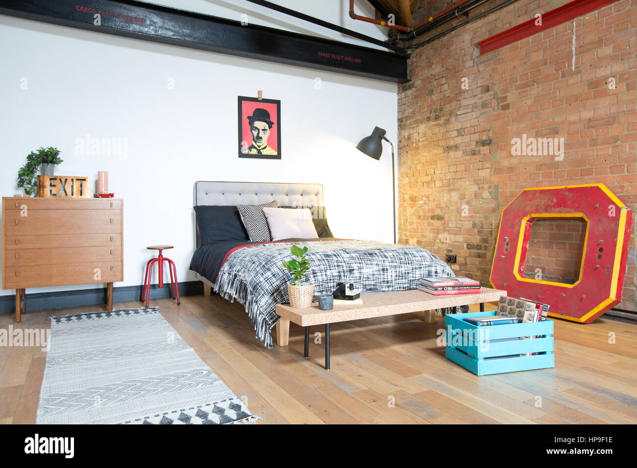 A bedroom in a loft style apartment with exposed brick and ...