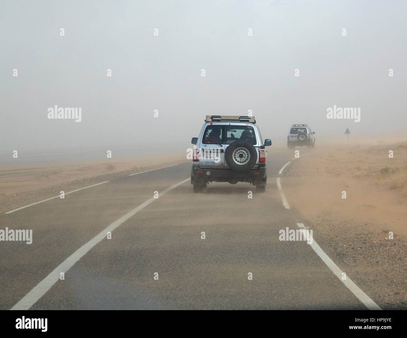 Merzouga, Morocco.  Wind Blows Sand Across the Road as vehicles Leave Merzouga. - Stock Image