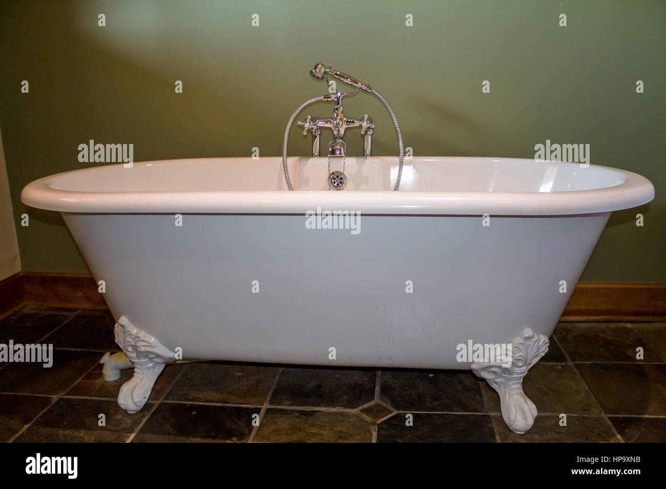 Vintage type footed white bath tub in olive green bathroom with slate tile floor - Stock Image
