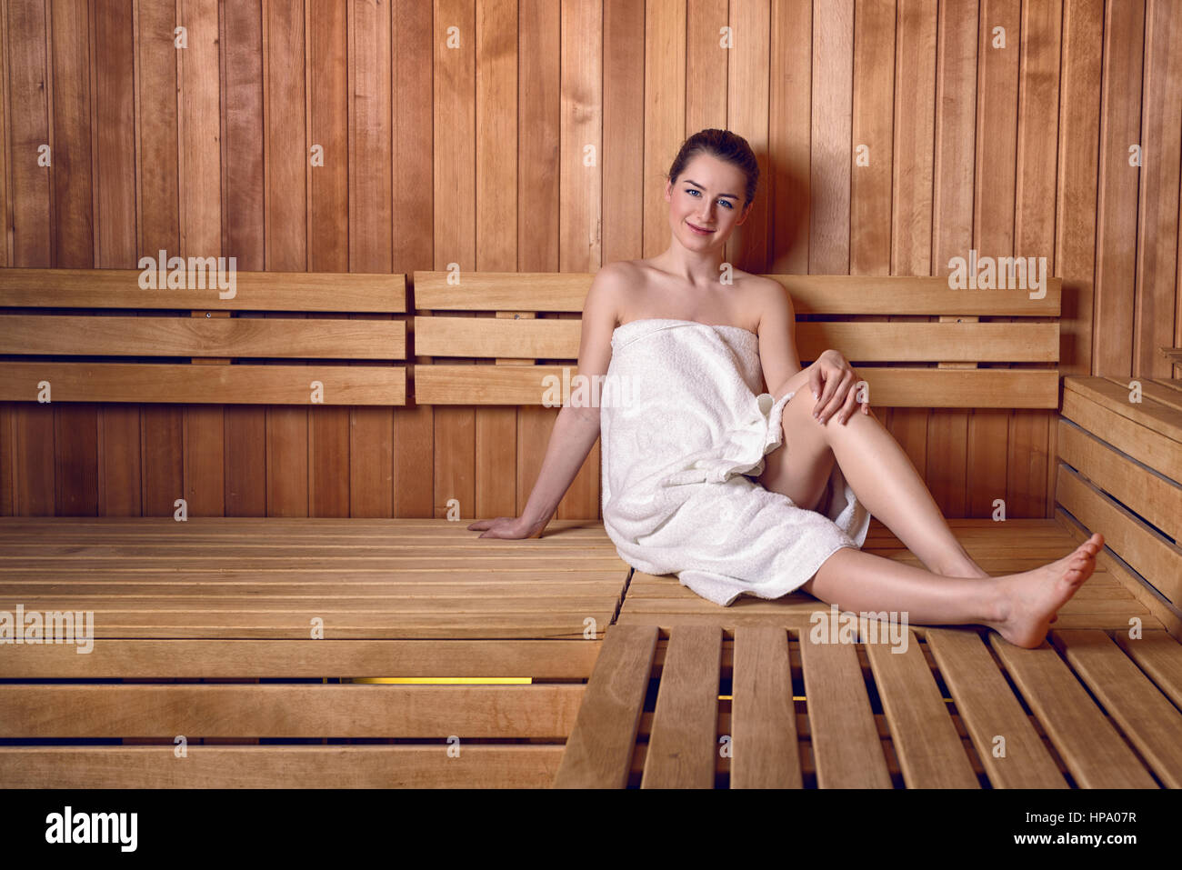 Side view full length portrait of young woman smiling sitting on wooden sofa bench in sauna wrapped in white towel, - Stock Image