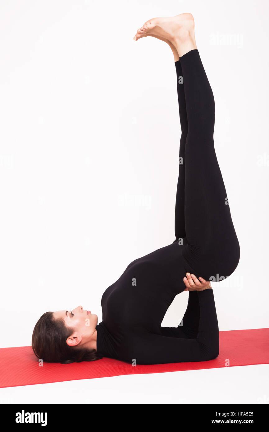 Beautiful athletic girl in a black suit doing yoga. salamba sarvangasana asana - Stand on the blades . Isolated - Stock Image