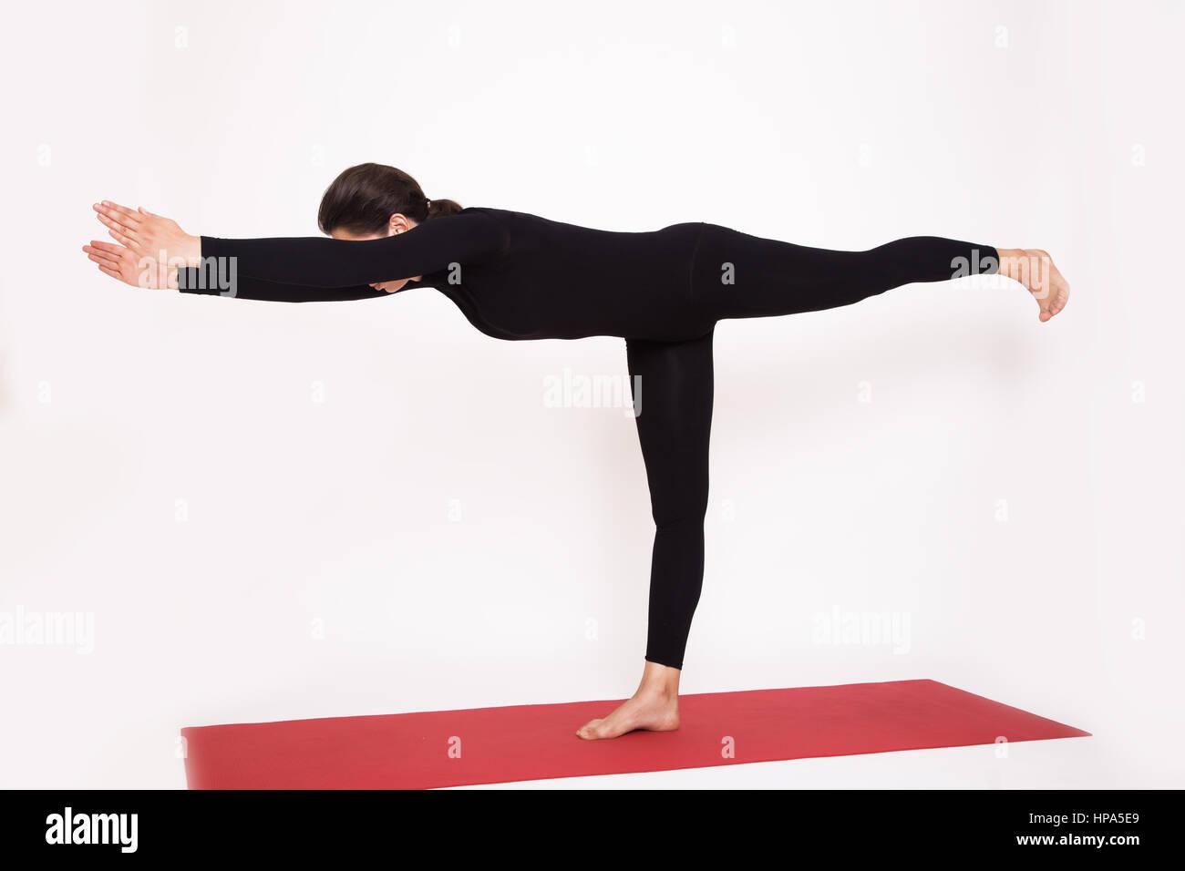 Beautiful athletic girl in a black suit doing yoga. Virabkhadrasana asana - warrior pose . Isolated on white background. - Stock Image