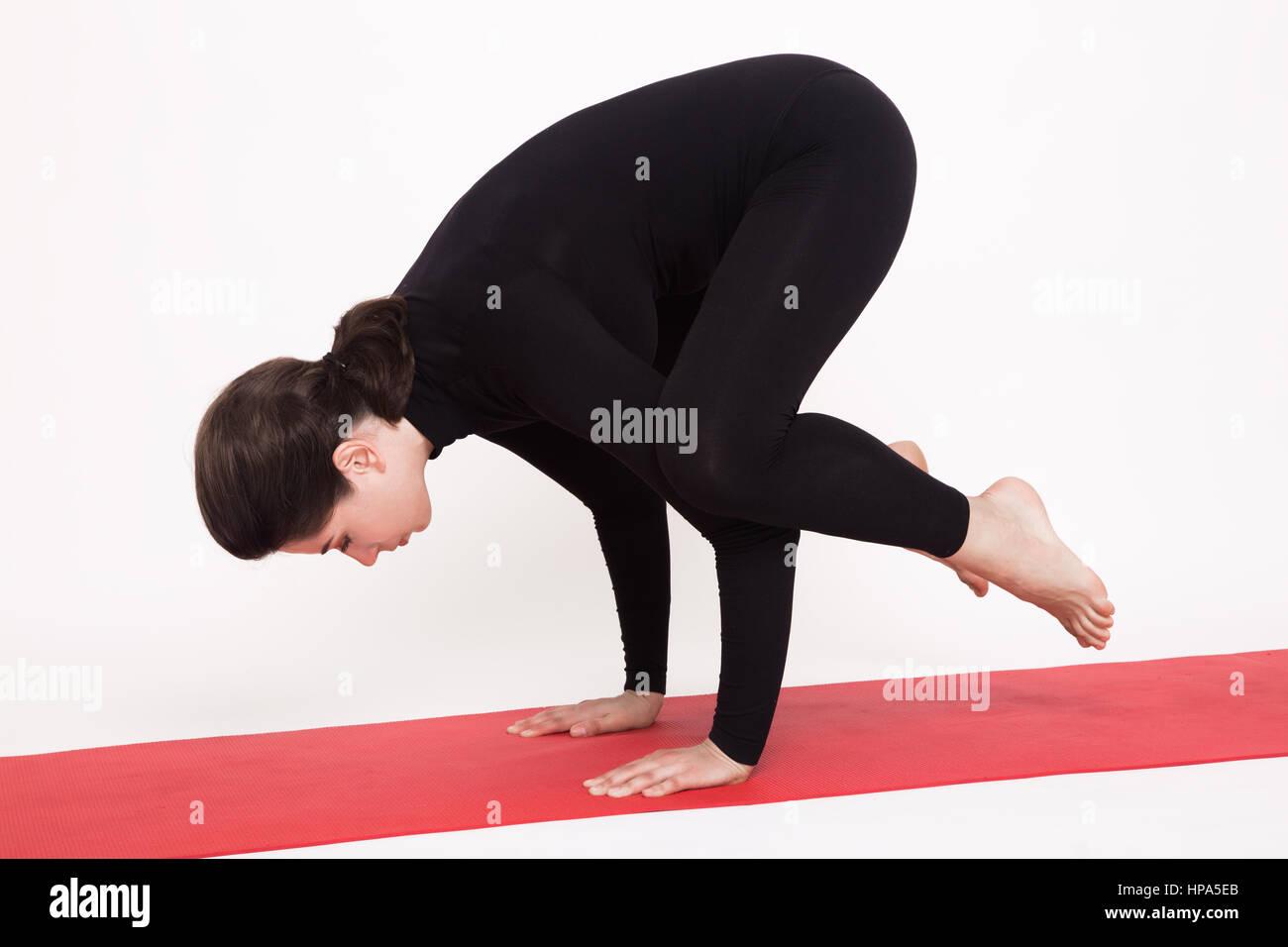 Beautiful athletic girl in a black suit doing yoga. Kakasana asana - crow pose . Isolated on white background. - Stock Image
