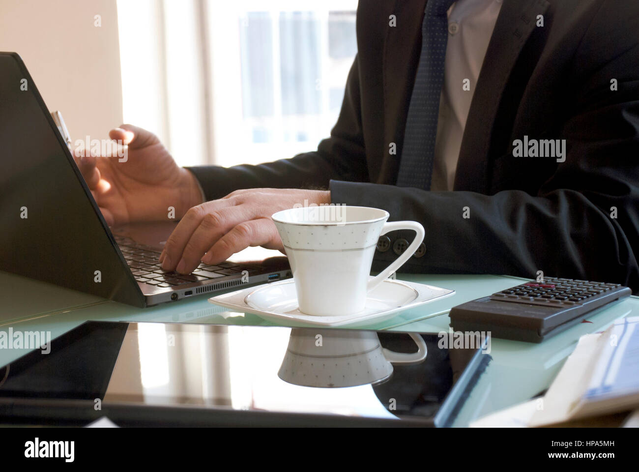Businesman working from home on a with laptop computer - Stock Image
