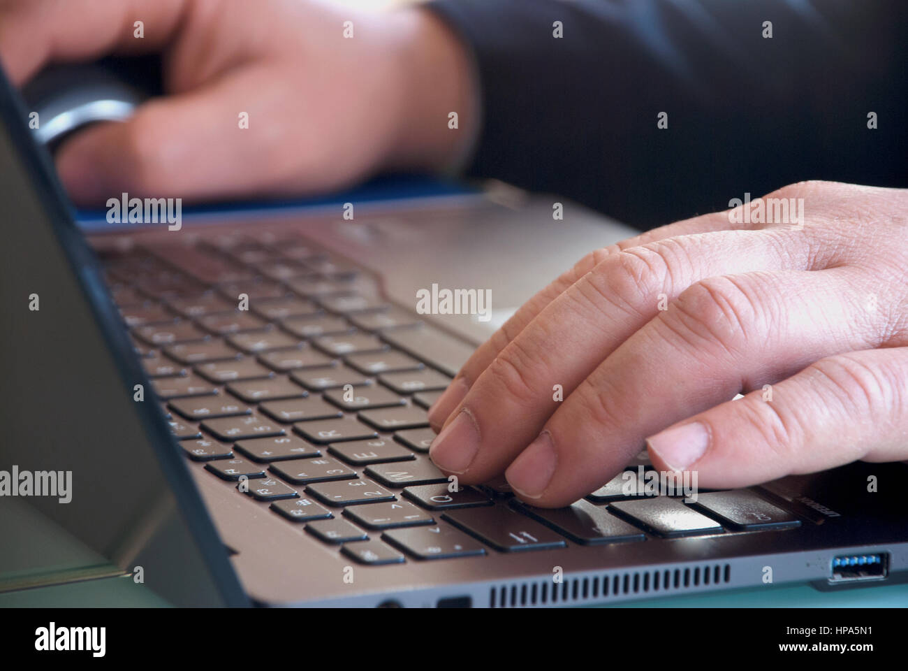 Businessman close-up view of the hands on the laptop keyboard - Stock Image