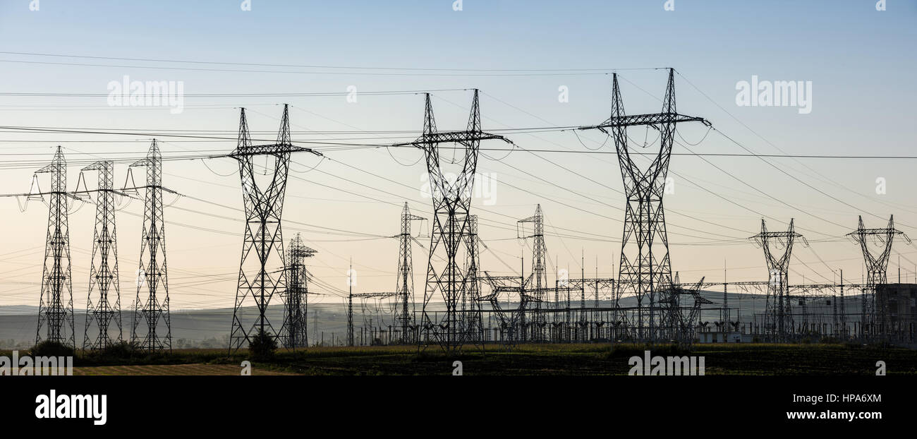 Electricity transmission pylon silhouetted against blue sky at dusk. - Stock Image