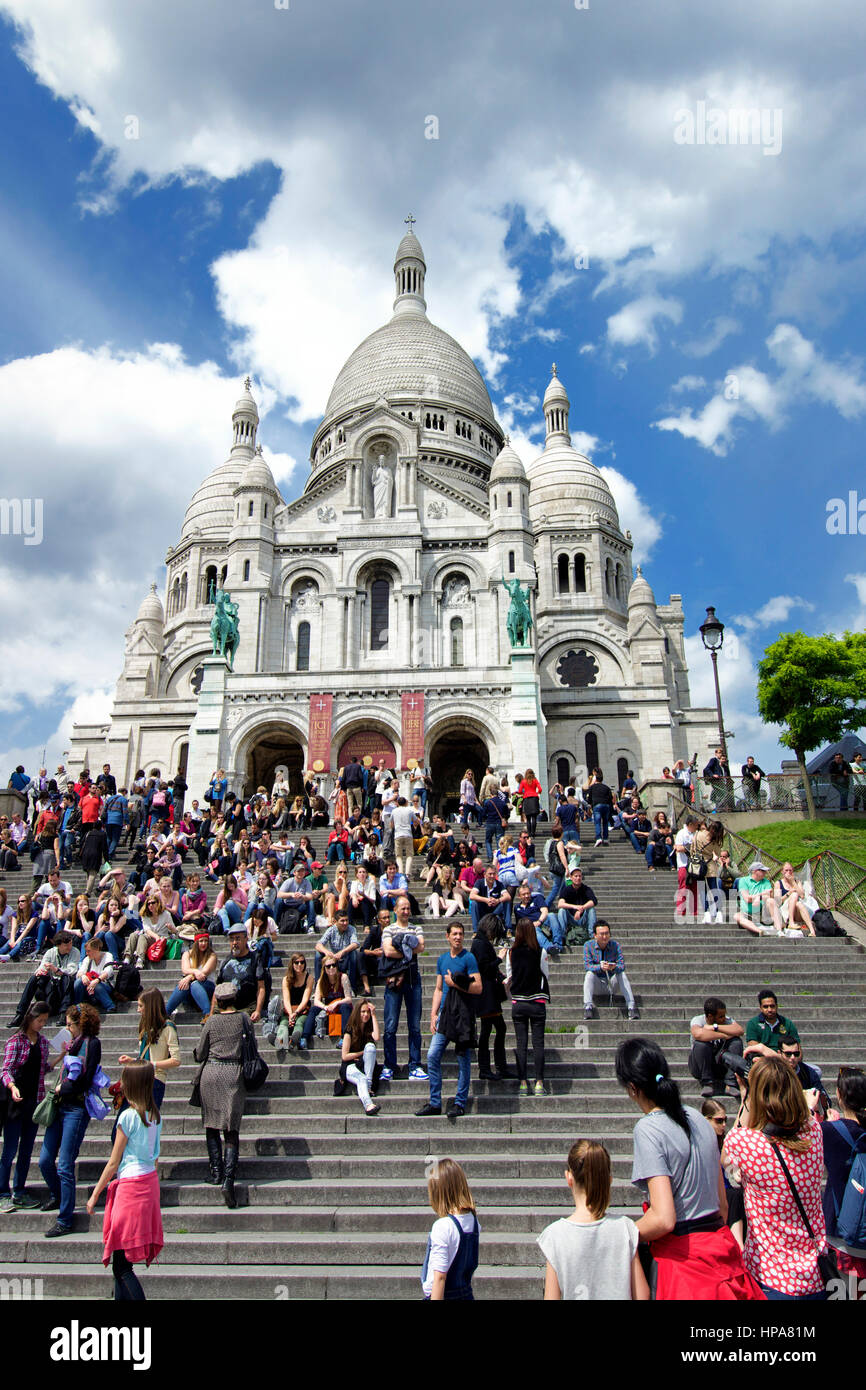 Sacre Coeur Basilica, Montmartre, Paris, France with tourists on the steps - Stock Image