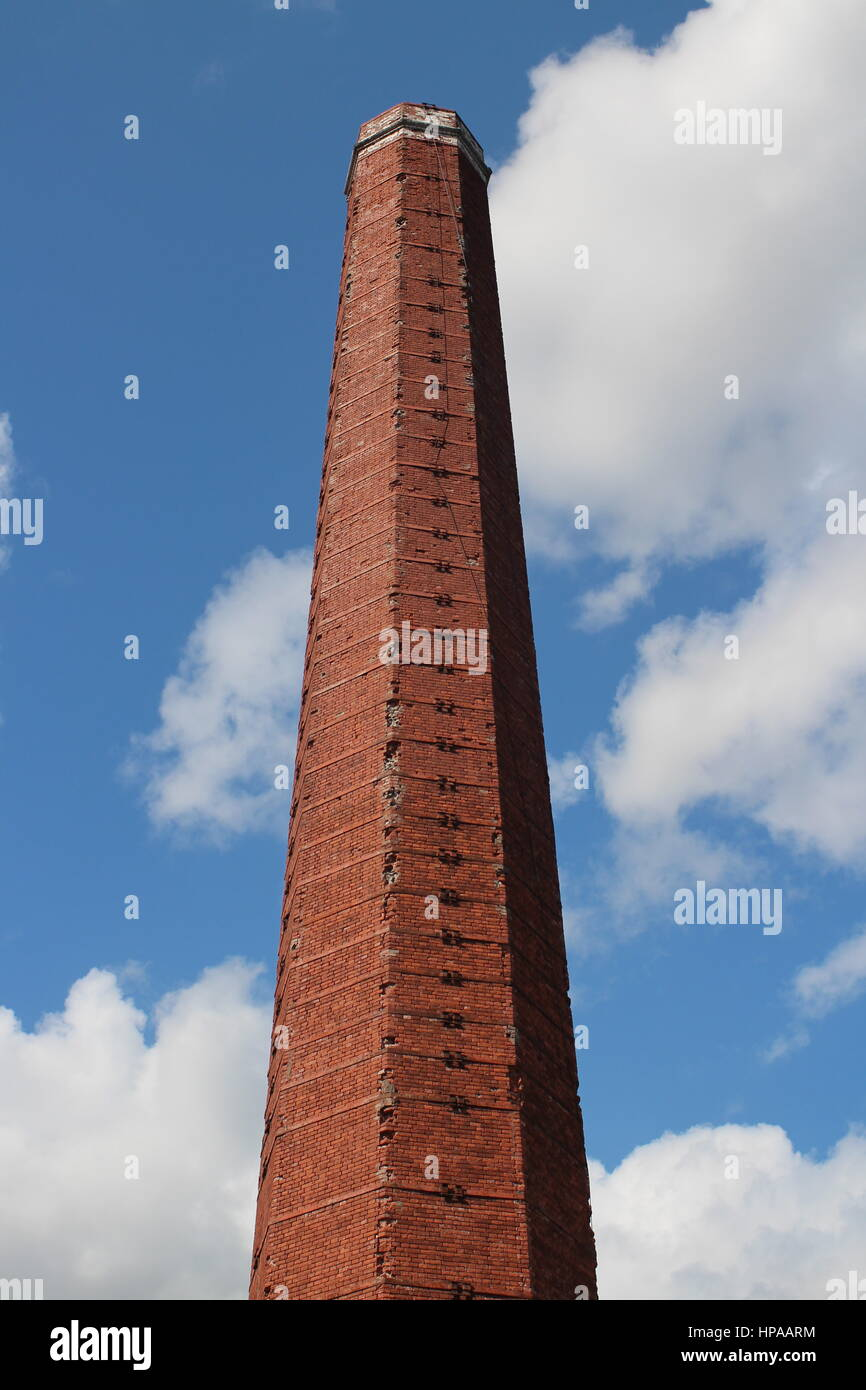 High polyhedron smokestack in the blue sky - Stock Image