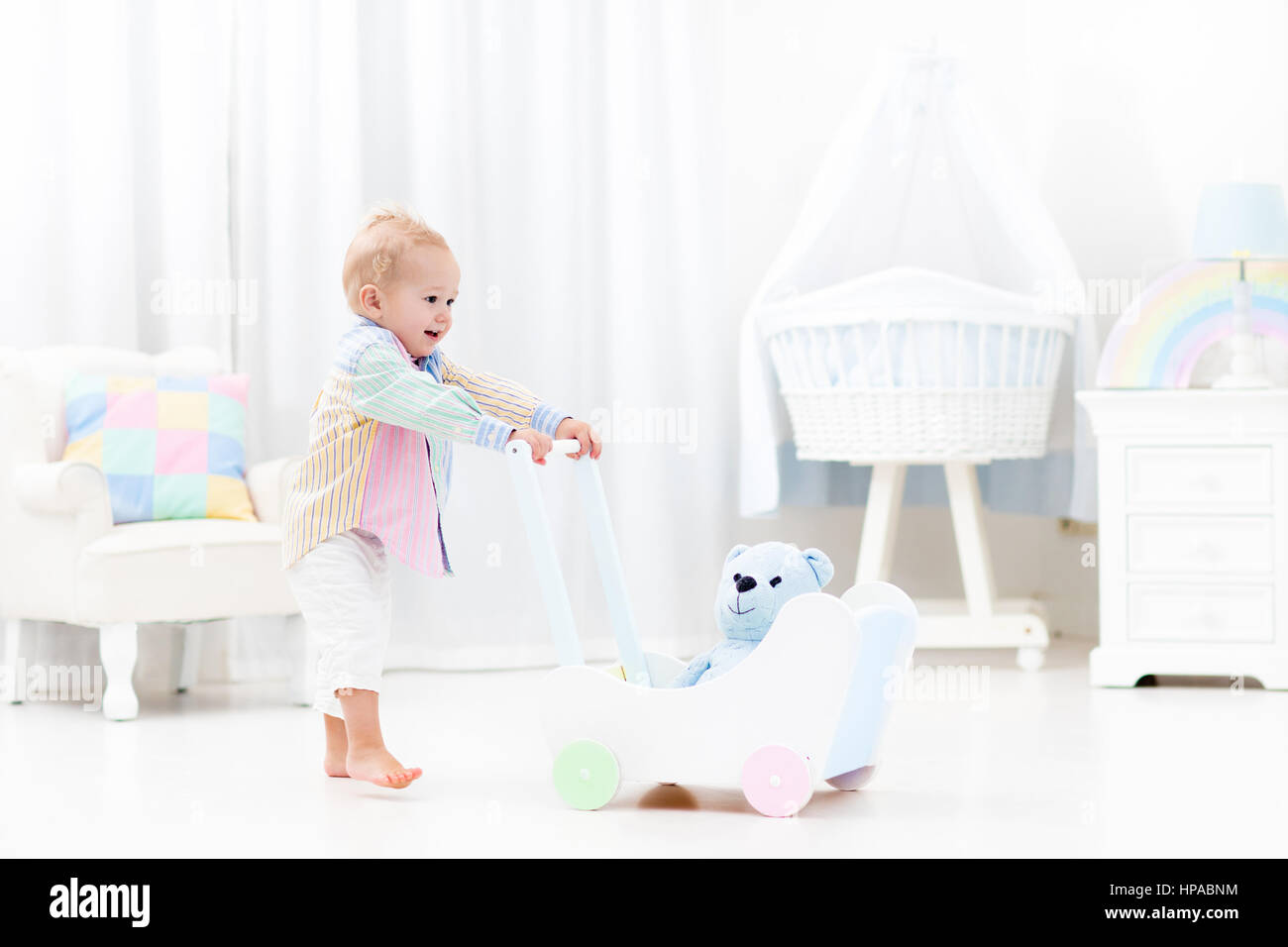 Baby boy learning to walk with wooden push walker in white bedroom with pastel rainbow color toys. Aid toy for child - Stock Image