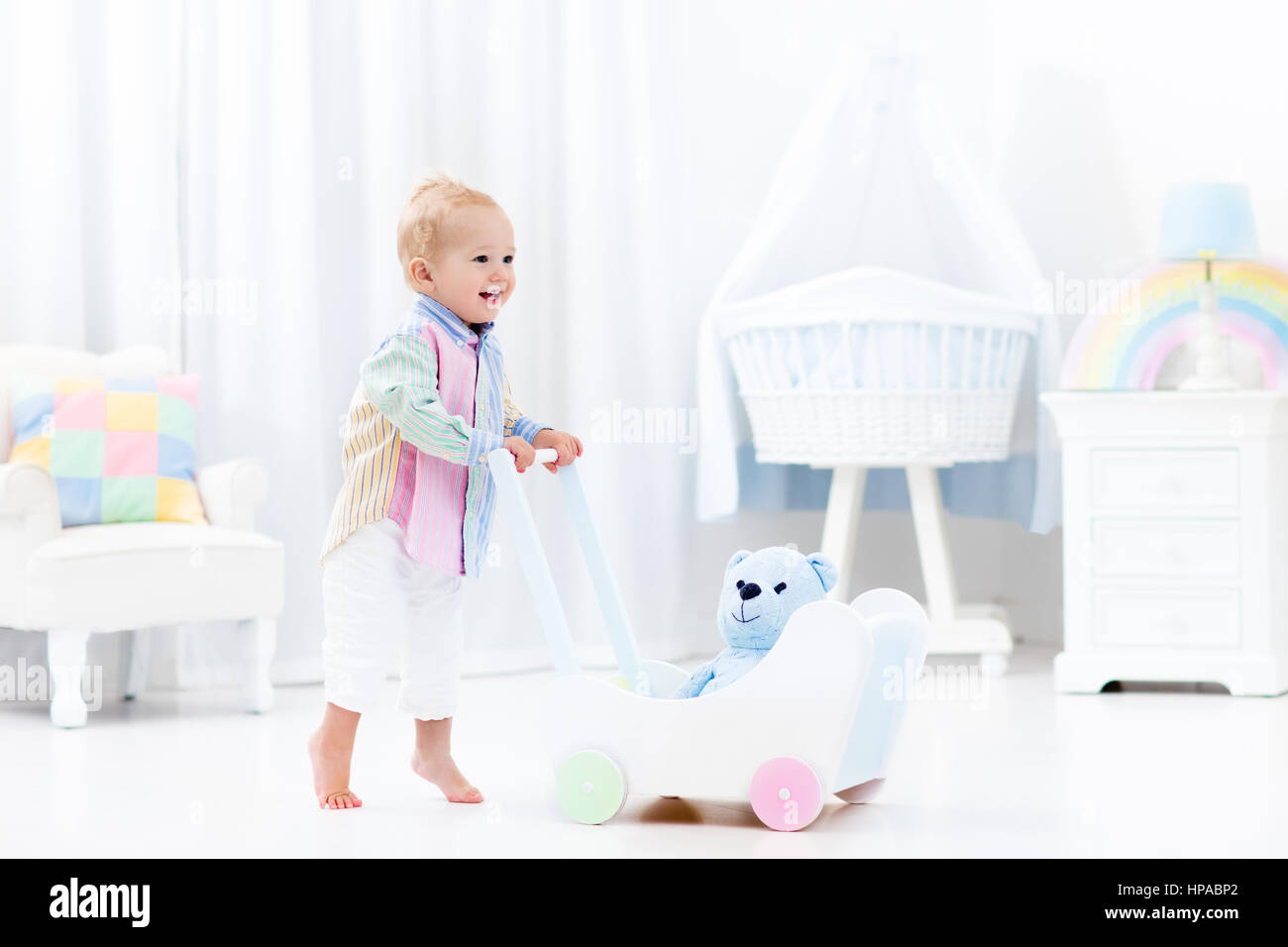 Baby boy learning to walk with wooden push walker in white bedroom with  pastel rainbow color