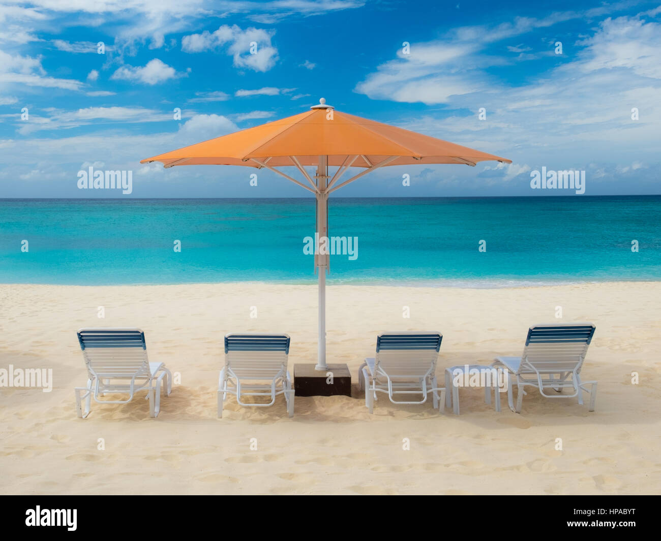 Parasol And Sun Loungers On Seven Mile Beach in the Caribbean, Grand Cayman, Cayman Islands - Stock Image