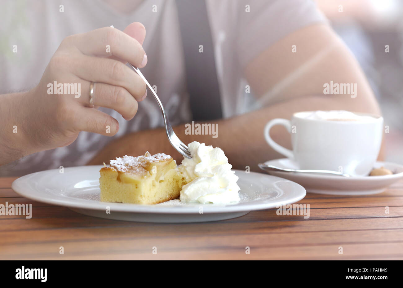 Piece Of Creamy Sweet Cake cut a man's hand with a fork. - Stock Image