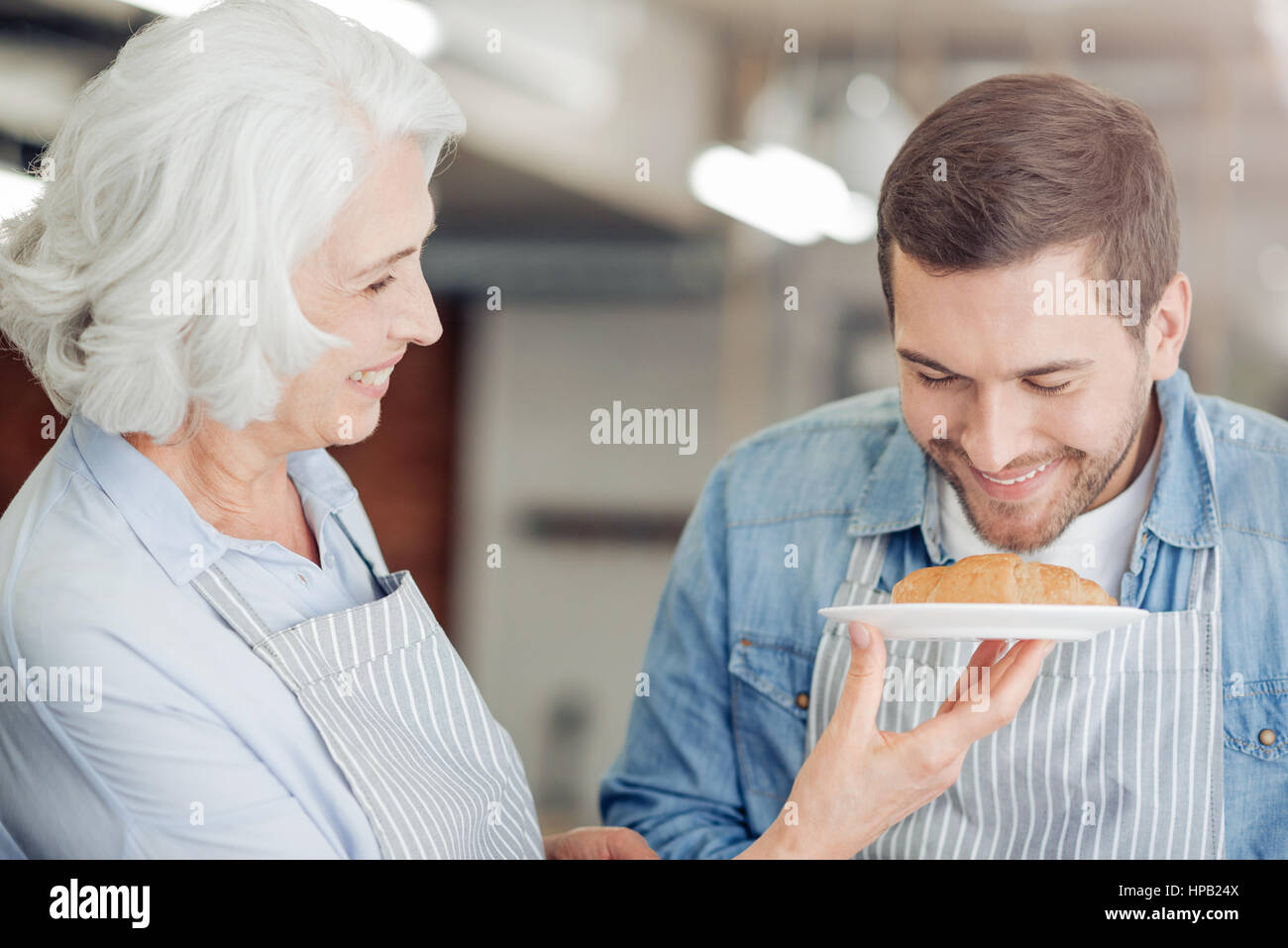 So tasty. Pleasant delighted mna smelling freshly baked croissant and going to cook it with her gradmother - Stock Image