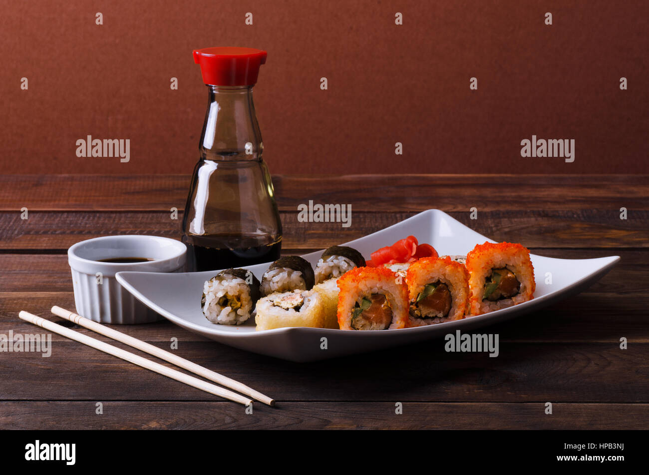 Sushi roll on a plate with soy sauce and chopsticks - Stock Image