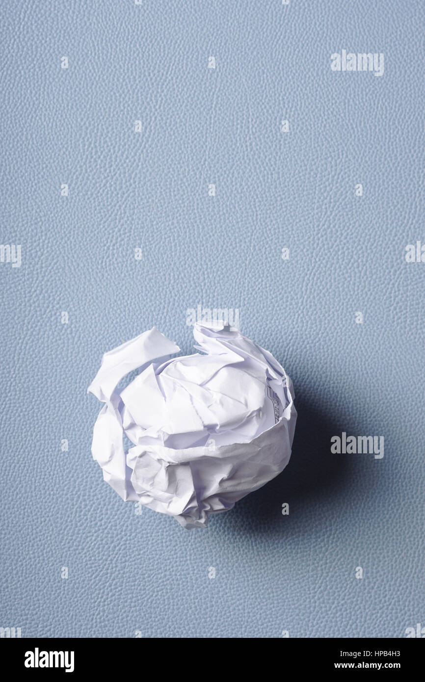 crumpled-up ball of paper on blue background - Stock Image