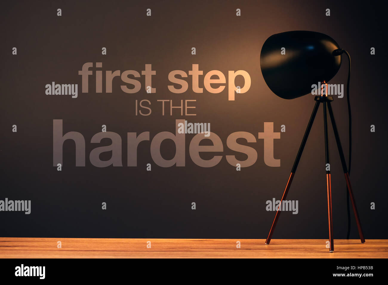 First step is the hardest, motivational message on office wall illuminated by the desk lamp - Stock Image
