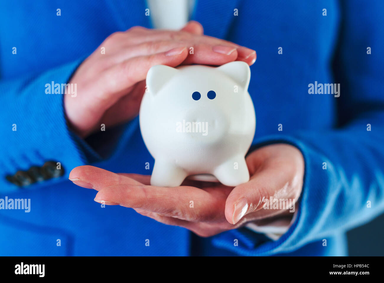 Woman cuddles piggy coin bank, responsible home budgeting and money saving - Stock Image