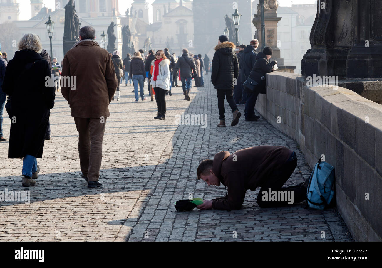 Young man begging with cap in hand on the Charles Bridge in Prague Czech Republic winter - Stock Image