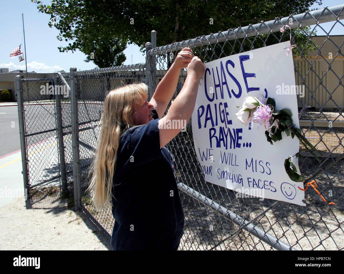 Sharron Russo affixes a sign memorializing Chase, Paige and Rayne McGowan, to a fence in front of the Hamilton Elementary - Stock Image