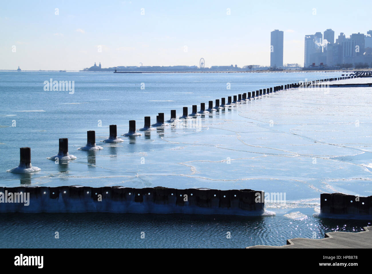 Wave breaking posts line up to lead to a cold, wintery view of the Chicago skyline and frozen Lake Michigan during - Stock Image