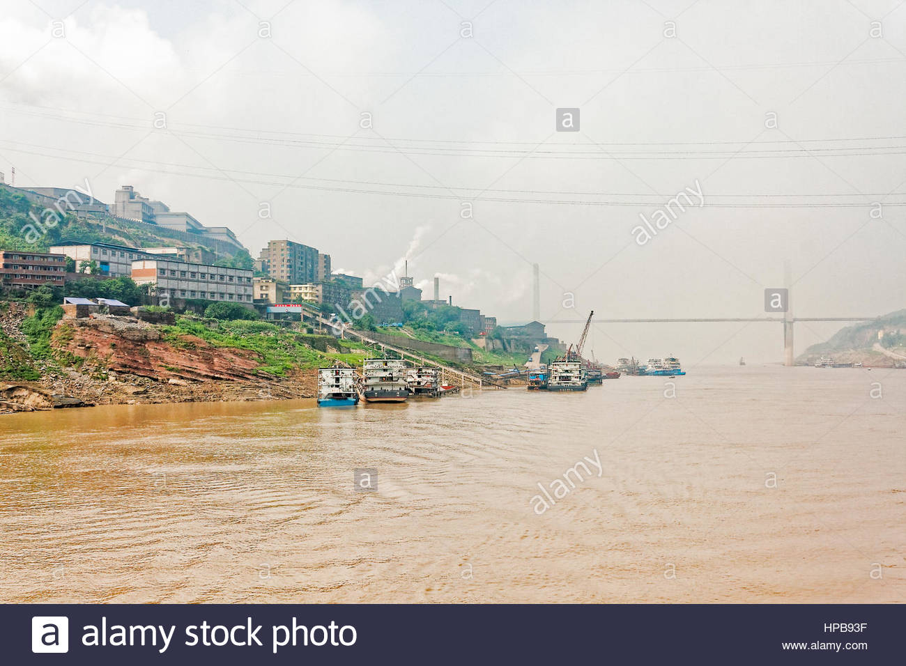 Factories on the banks of the Yangtze River, near the town of Fuling, on a hazy morning - Stock Image