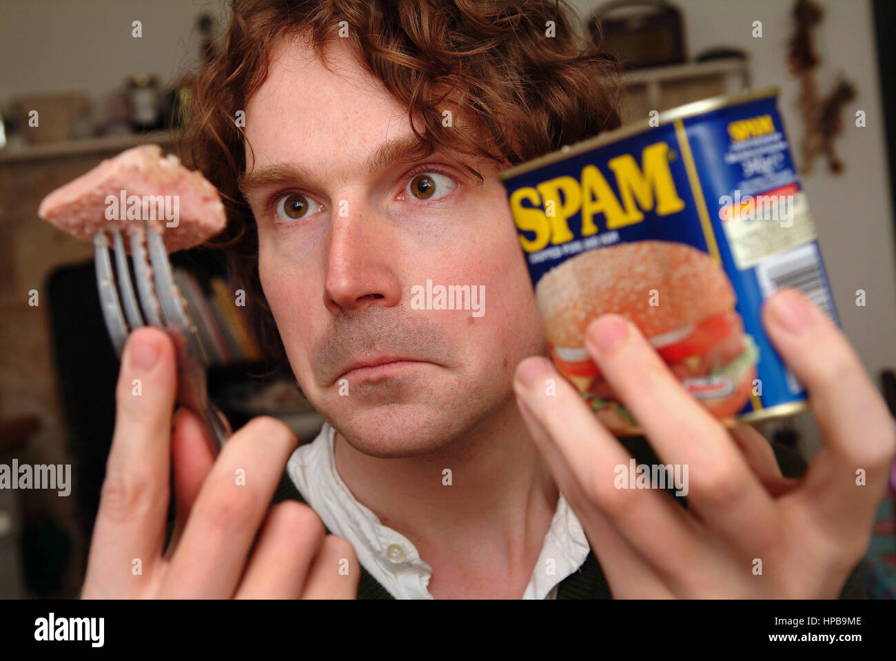 Tom Payne with a can of Spam (spicey ham) and a recreation of a wartime Spam meal - Stock Image