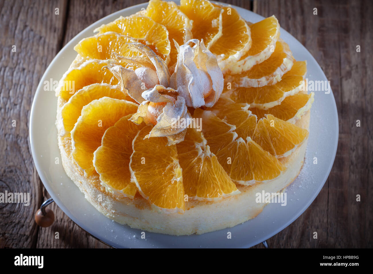 Cheesecake decorated with oranges and physalis on a table - Stock Image