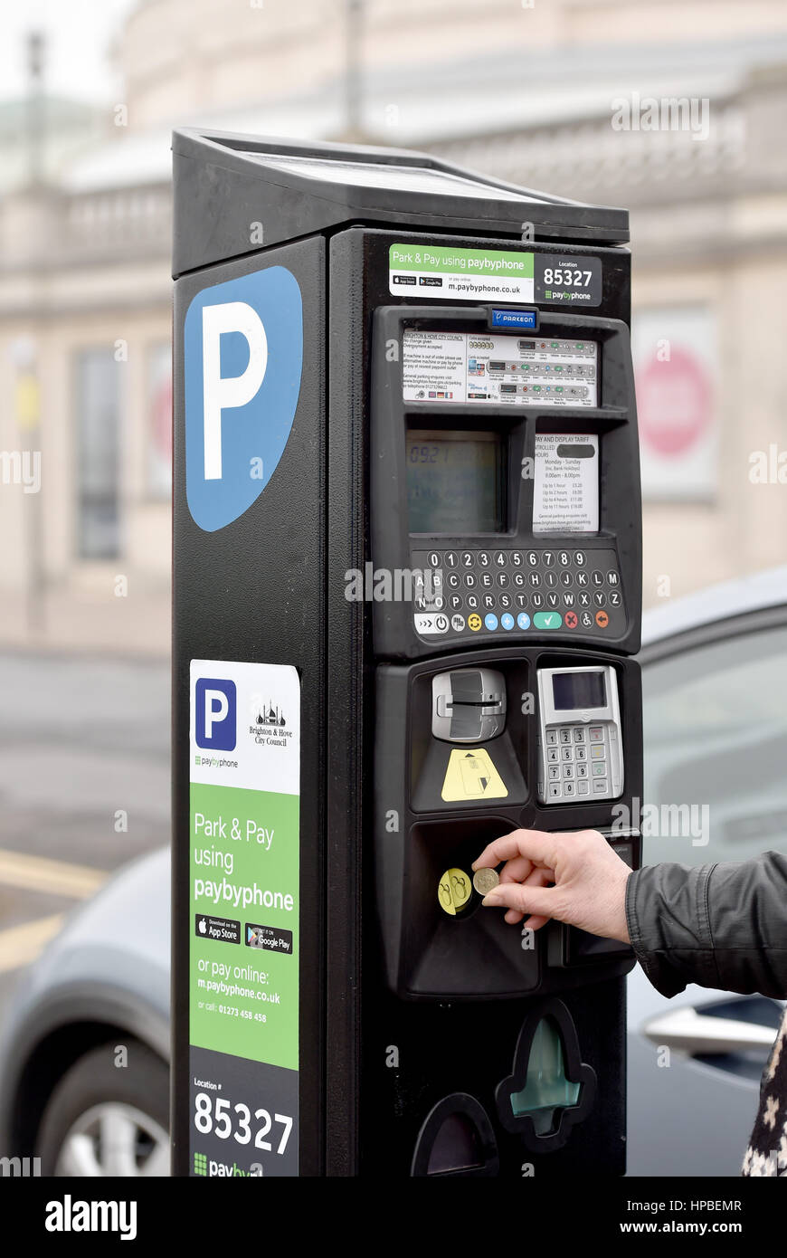 Woman paying for parking with one pound coin on Brighton seafront UK The old pound coin is soon to be replaced with - Stock Image