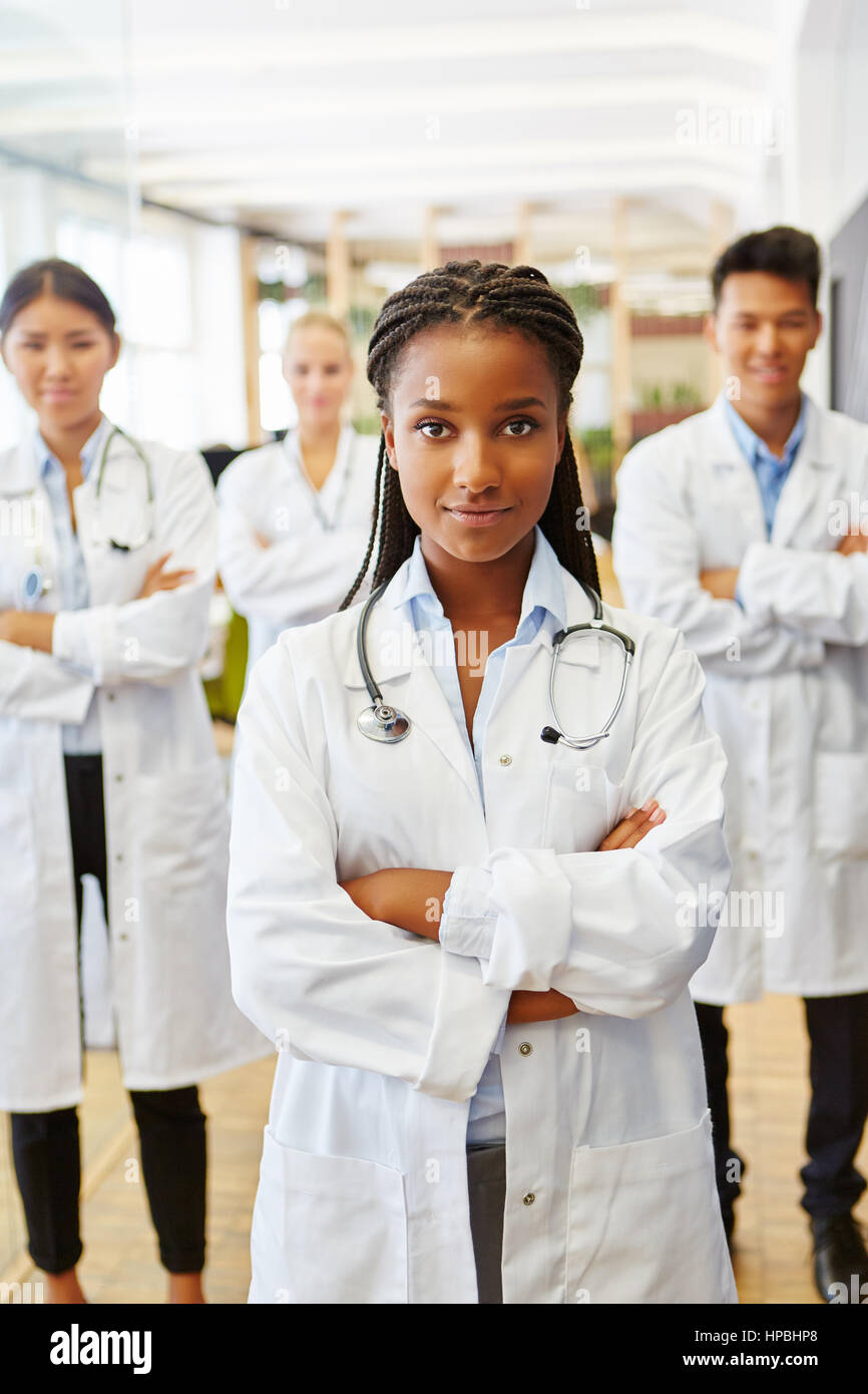 African doctor in medical school with interracial team of students - Stock Image
