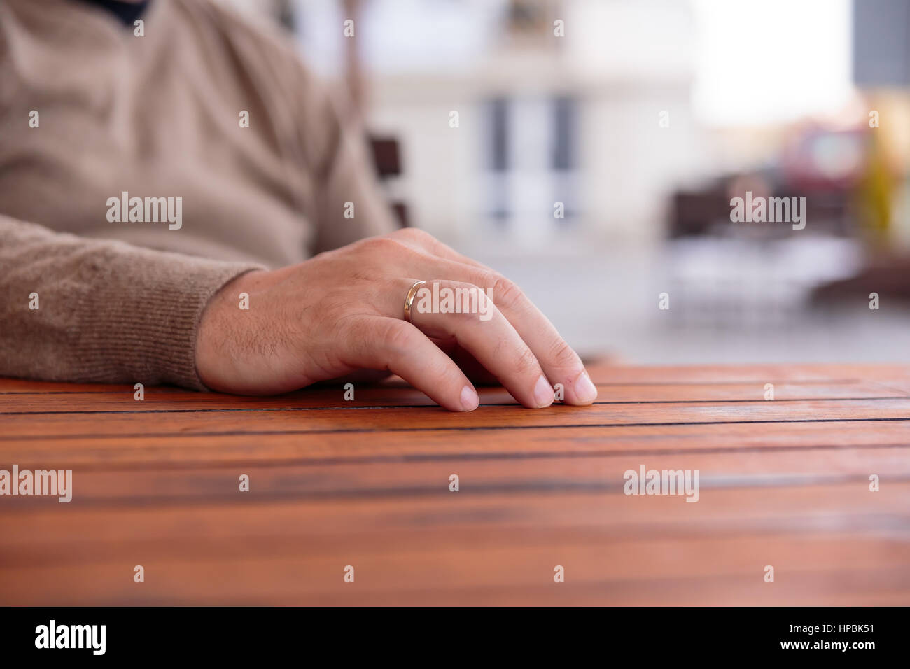 young man's hand with a gold wedding ring on  wooden table, blurred background - Stock Image