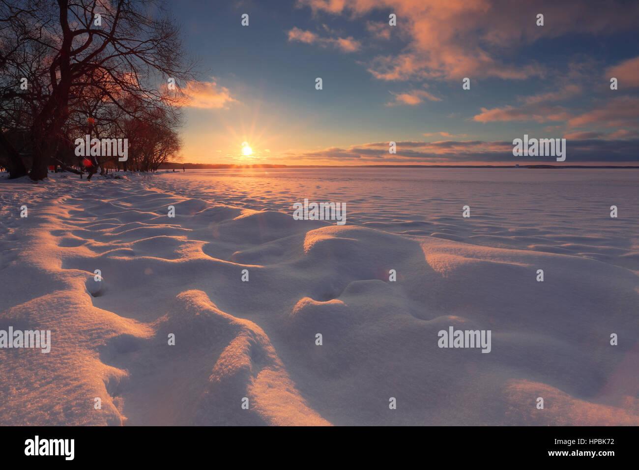 Winter sunrise background. Sun touch horizon. Sunlight illuminate snow. Colorful Christmas sky. - Stock Image