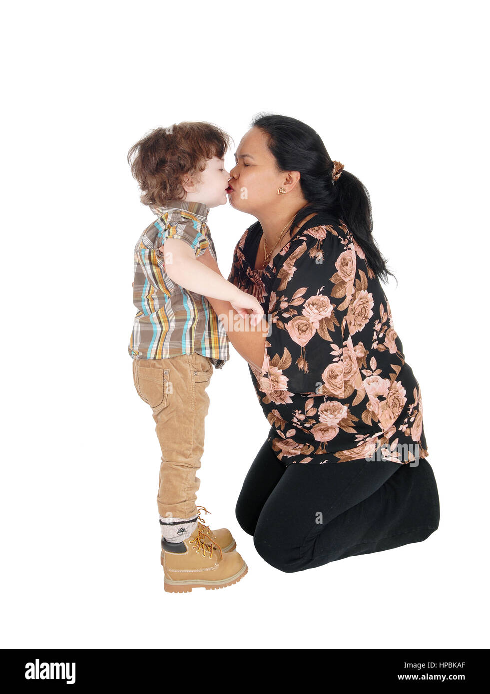 A Filipino nanny kneeling on the floor and kissing the little boy, standing in front of her, isolated for white - Stock Image