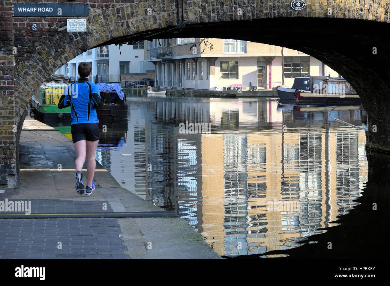 Back view of a jogger running under Wharf Road Bridge at City Basin Canal in Islington, East London E1 England UK Stock Photo