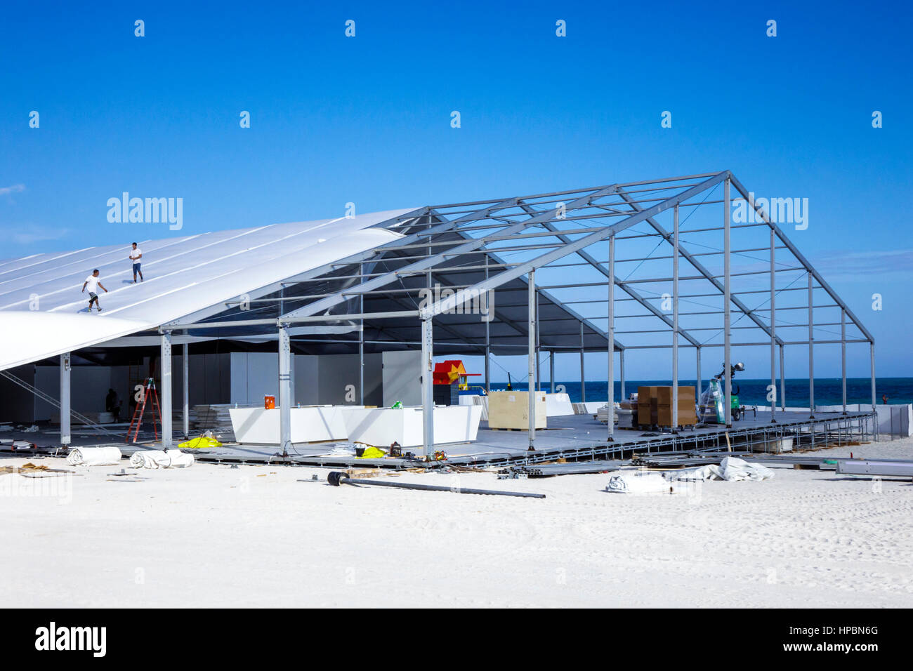 Miami Beach Florida Lummus Park Art Basel Week sand event tent assemble disassemble temporary building frame metal - Stock Image