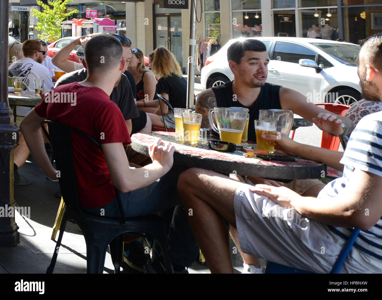 Young Aussie men enjoy their draft beer in a popular bar on Rundle street in Adelaide. - Stock Image