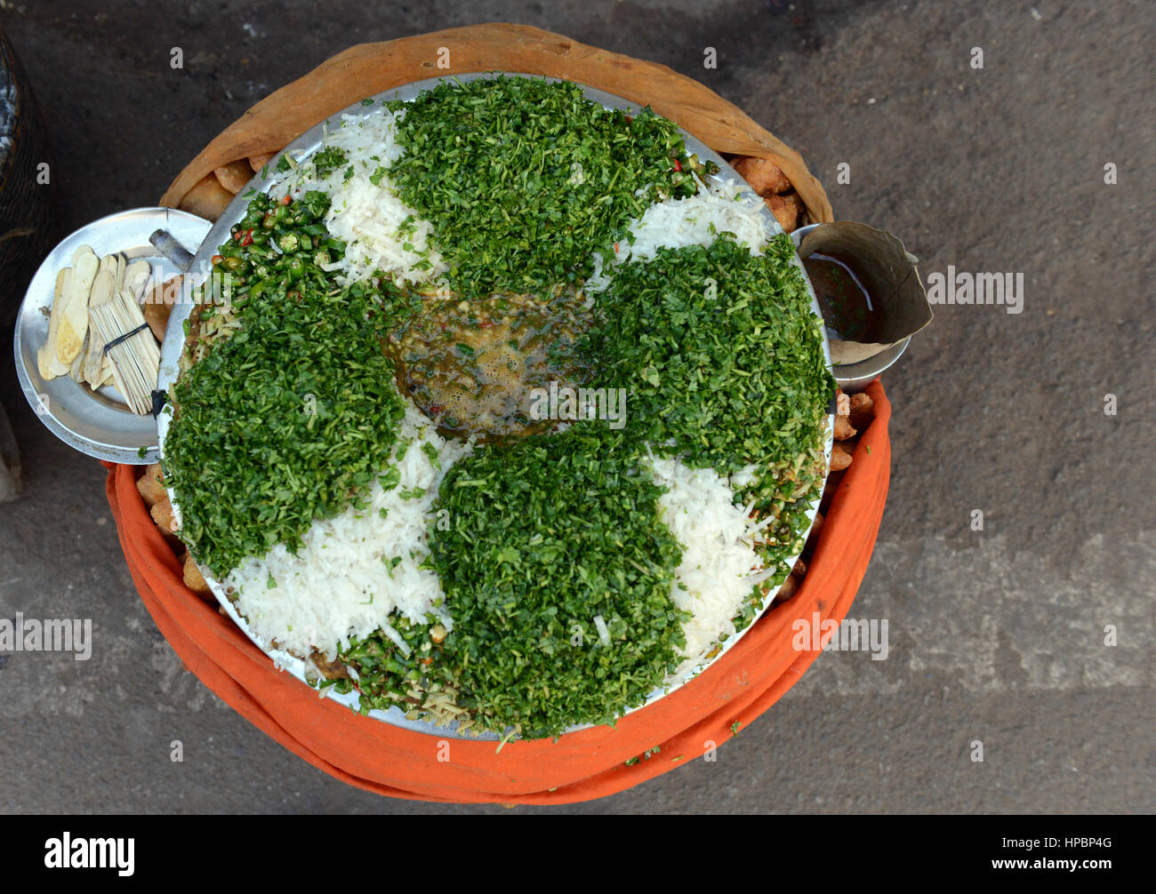 A street food vendor in Lucknow, India serving boiled chickpeas with onion and green garnish. - Stock Image