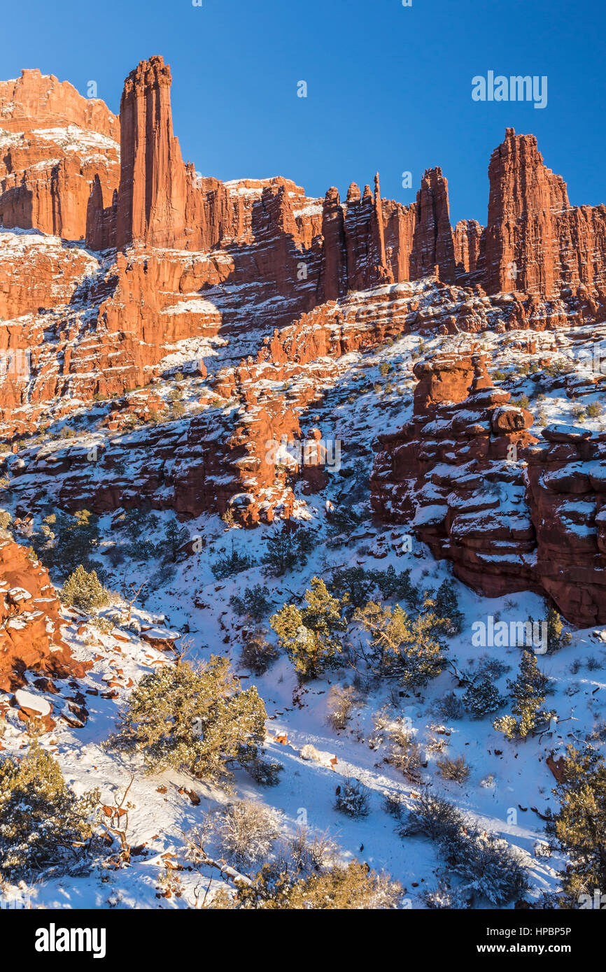 Rock fins rise above the a snowy canyon at the Fisher Towers rock formations near Moab, Utah. - Stock Image