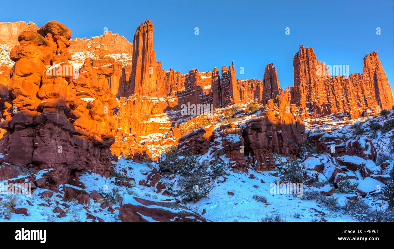 Rock fins rise above the a snowy canyon at the Fisher Towers rock formations near Moab, Utah - Stock Image