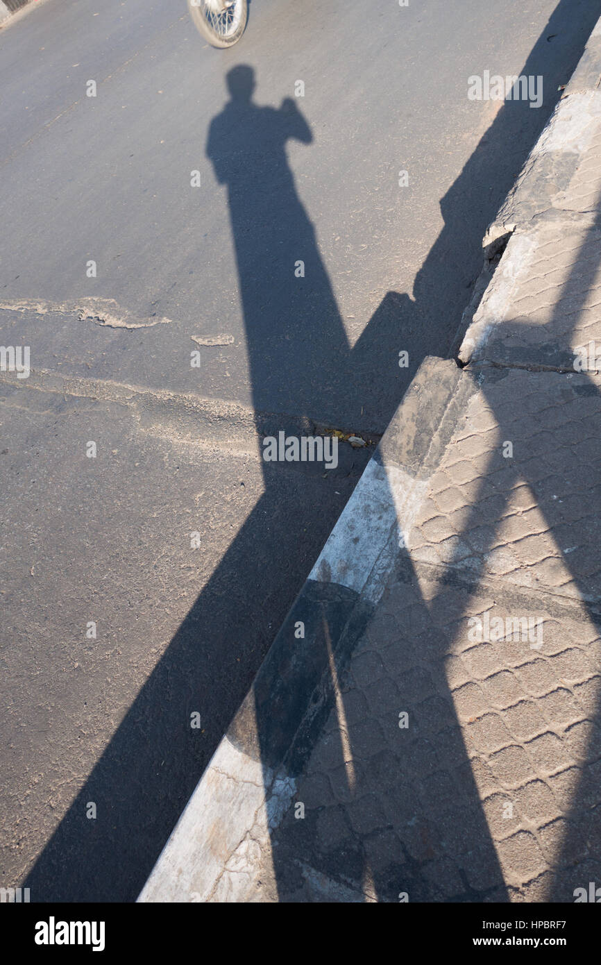 Indian man taking a picture of his own shadow standing on a sidewalk next to railing in Hyderabad,India Stock Photo