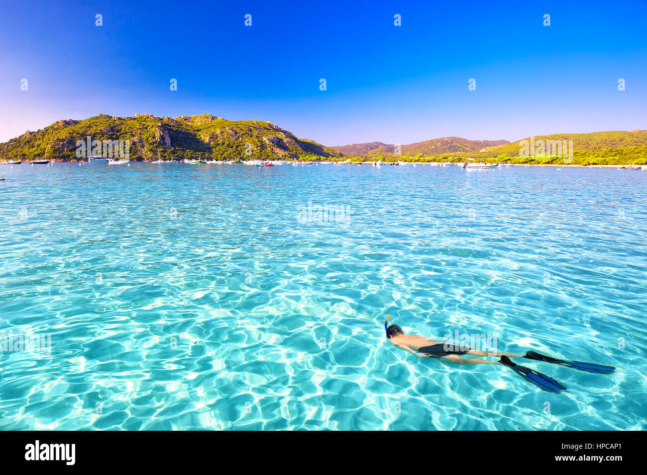 Young attractive man snorkeling in green lagoon in Santa Giulia sandy beach on the south part of Corsica, France, - Stock Image