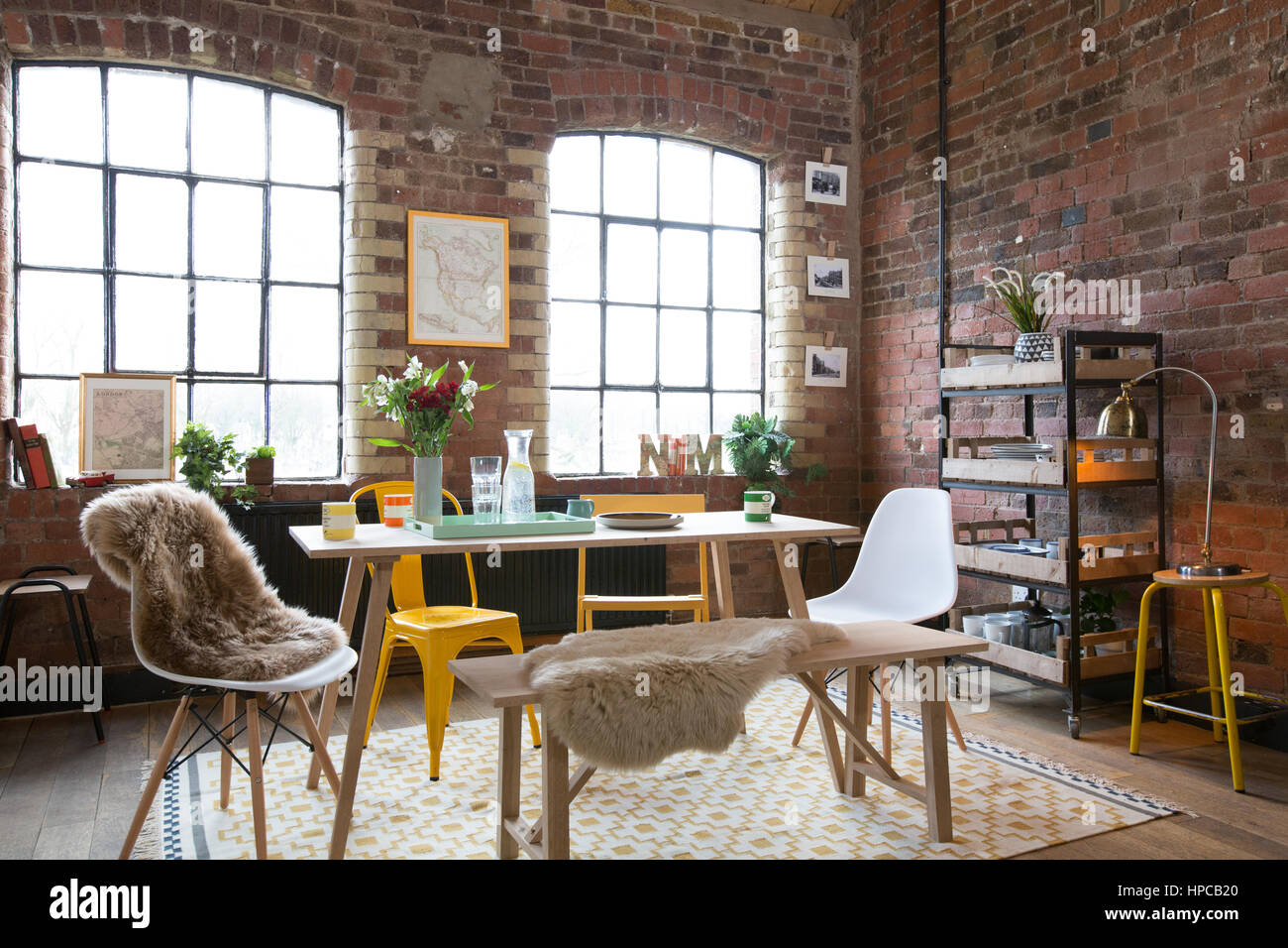 A dining room in a loft style apartment with exposed brick ...