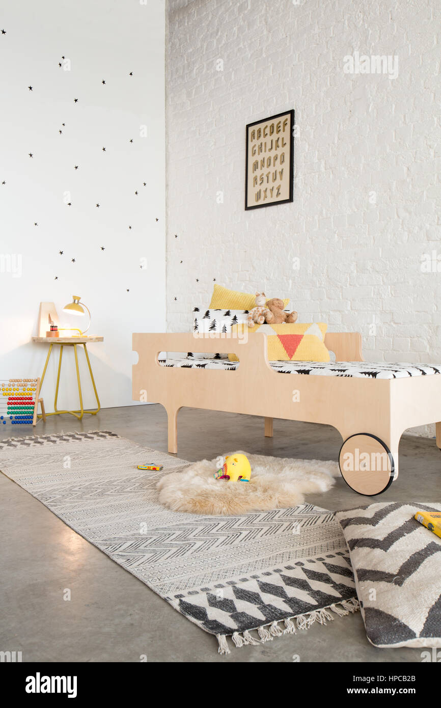 A bed in a child's bedroom with white walls and poured concrete floor Stock Photo
