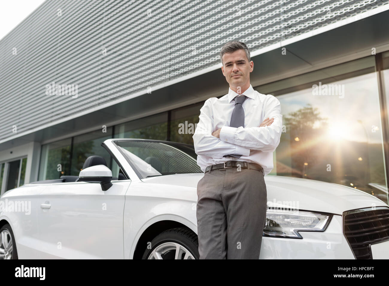 Confident car salesman leaning on a luxury convertible car, showroom on the background, dealership and business - Stock Image