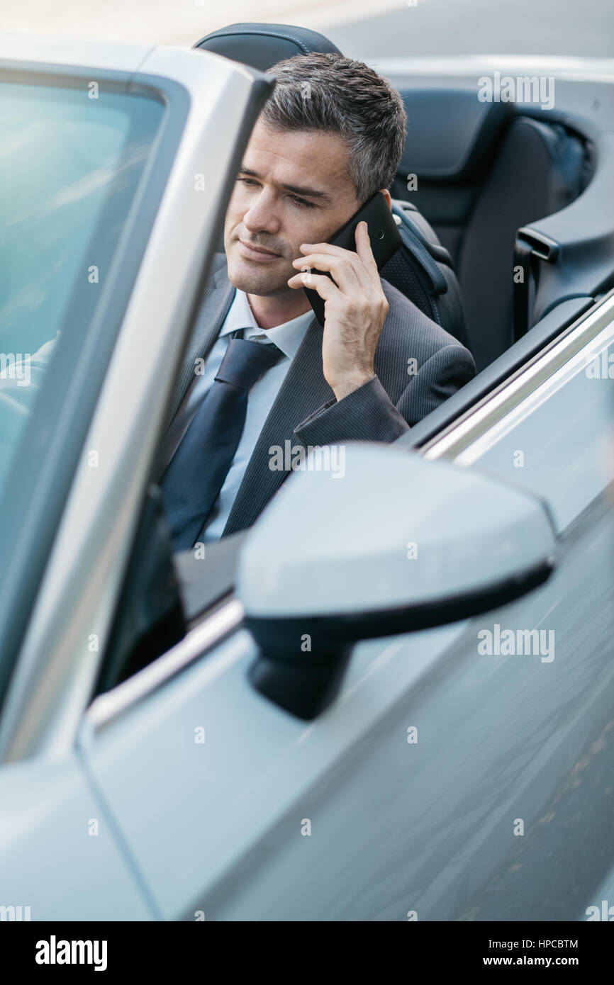 Businessman driving a luxury convertible car and having business phone calls using his smartphone - Stock Image