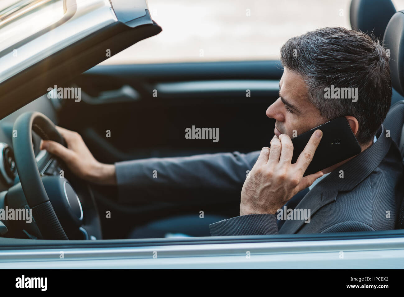 Businessman driving a luxury convertible car and having business phone calls using his smartphone Stock Photo