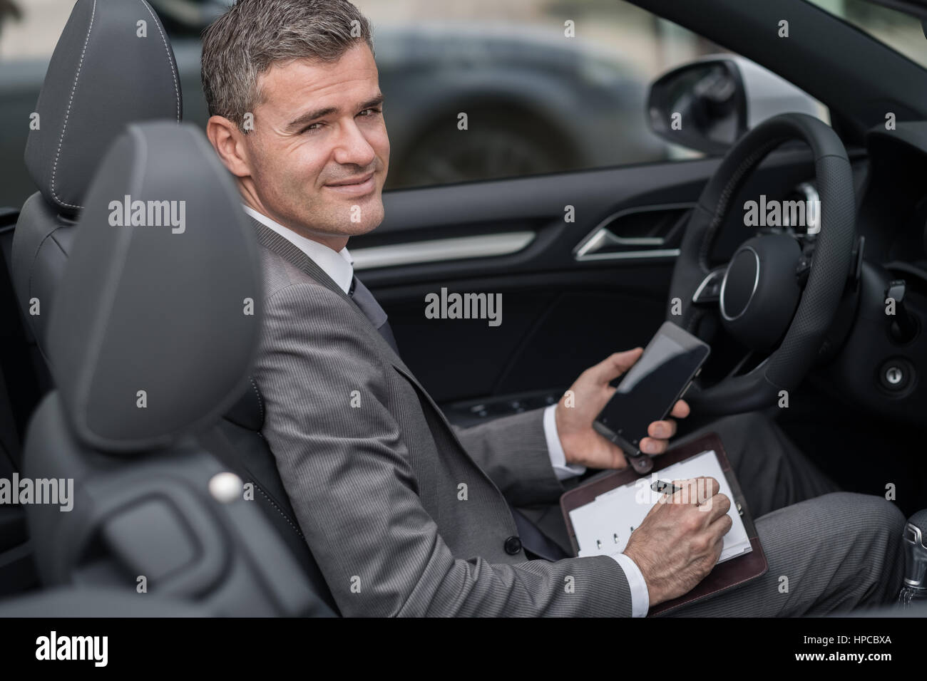 Businessman sitting in his car, he is planning and scheduling meetings on his organizer and using apps on his smartphone - Stock Image