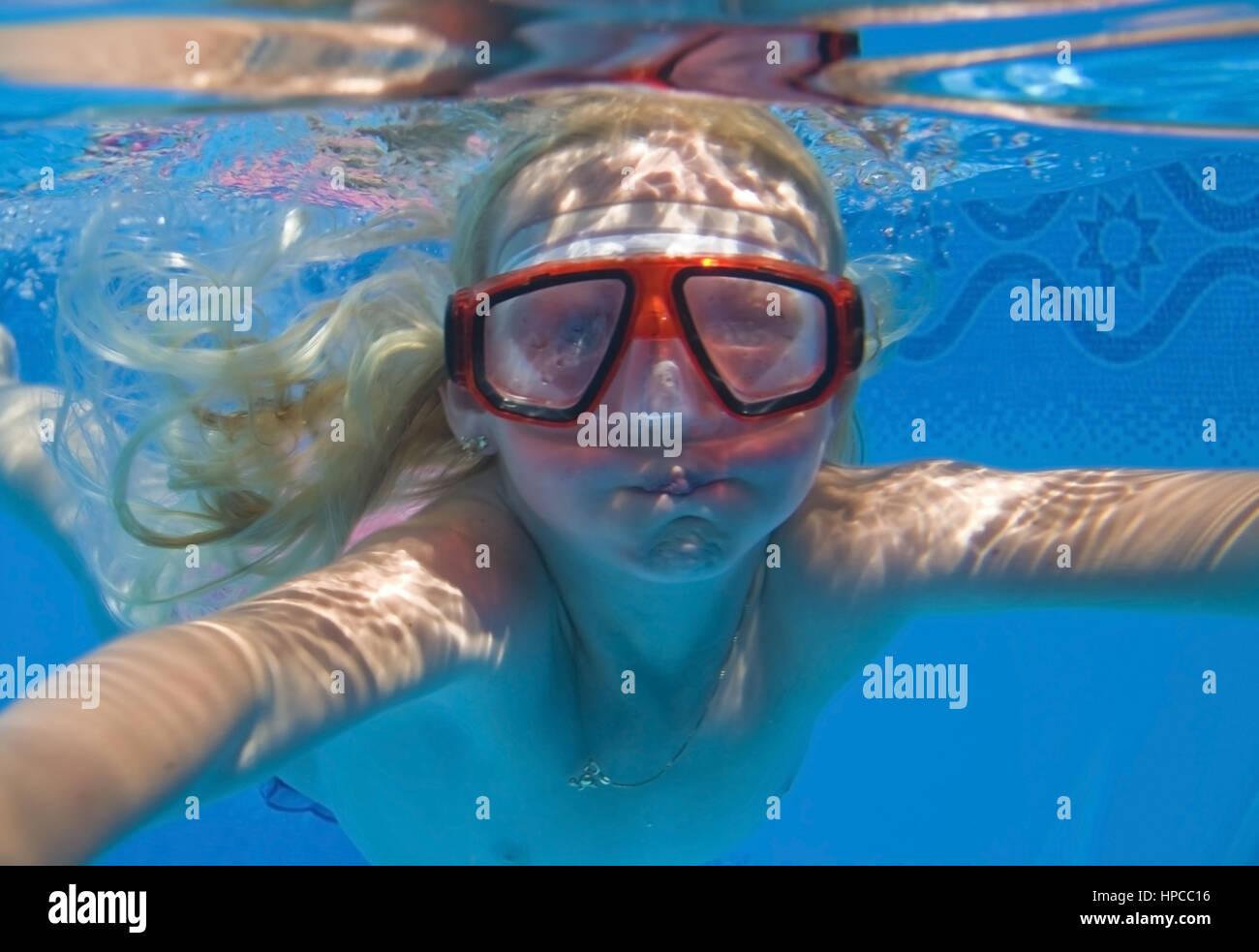 Maedchen mit Taucherbrille schwimmt Unterwasser - girl with diving googles swims under water Stock Photo