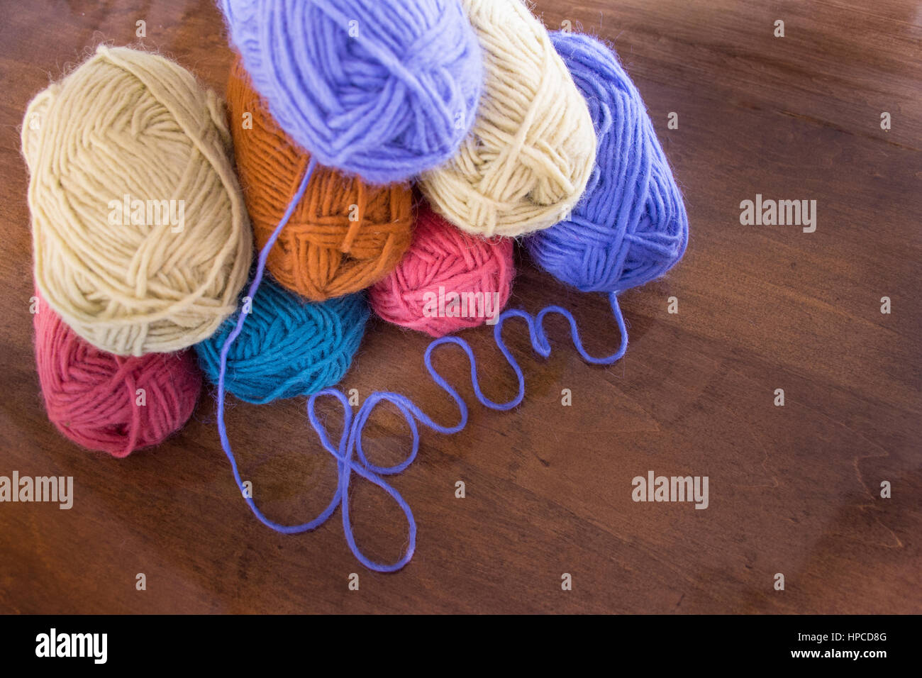 Eight skeins of lavender, cream, gold, turquoise and coral pink wool yarn stacked on a wooden table with the lavender - Stock Image