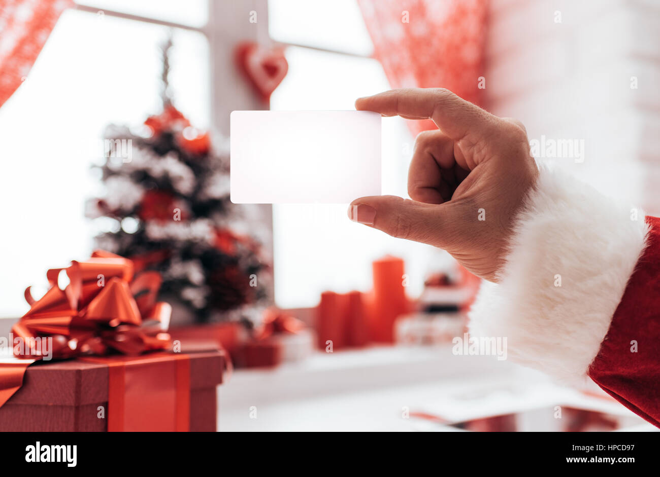 Santa claus holding a blank business card window and christmas santa claus holding a blank business card window and christmas decorations on the background colourmoves