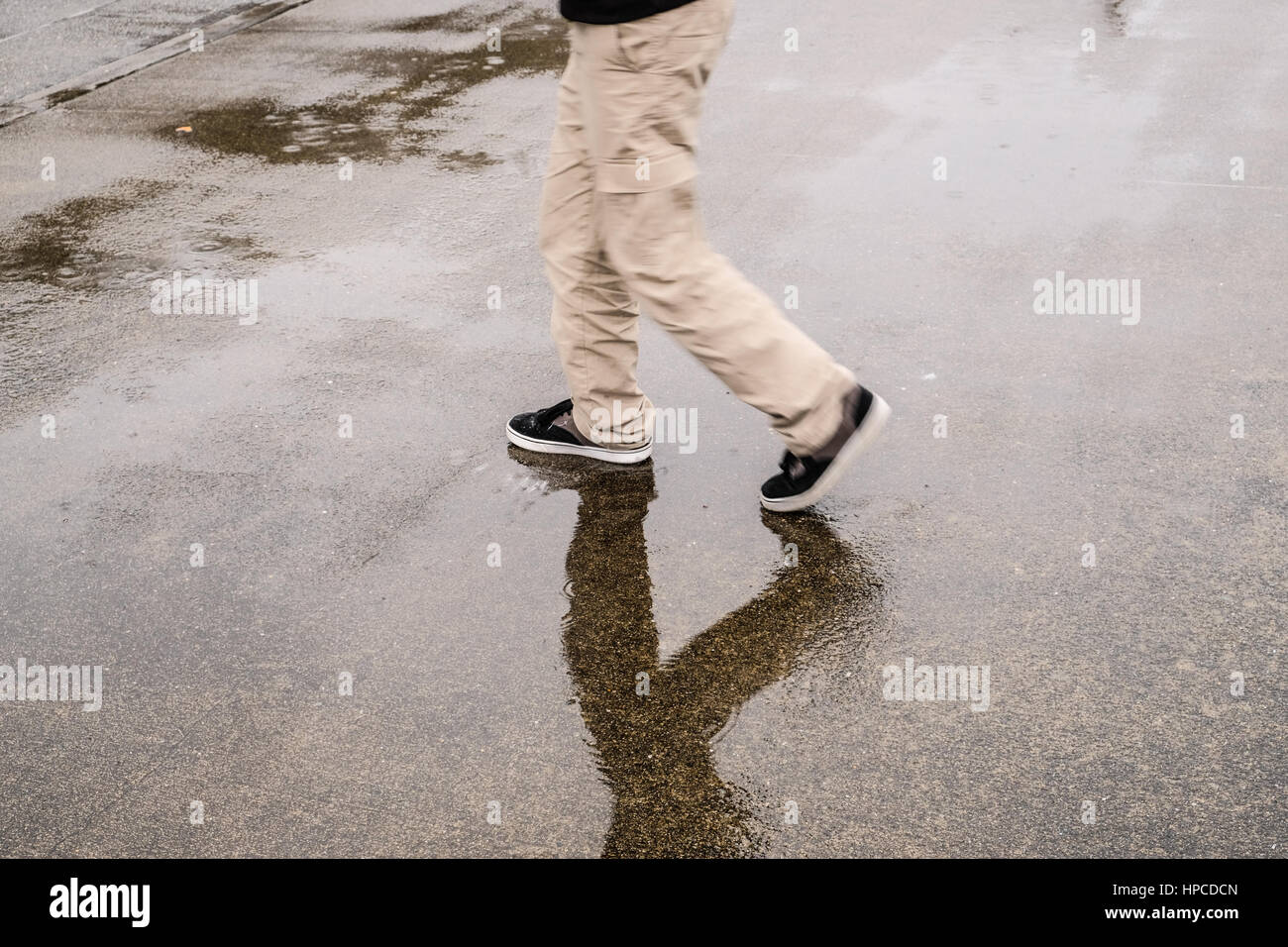 A boy walking in the rain - Stock Image